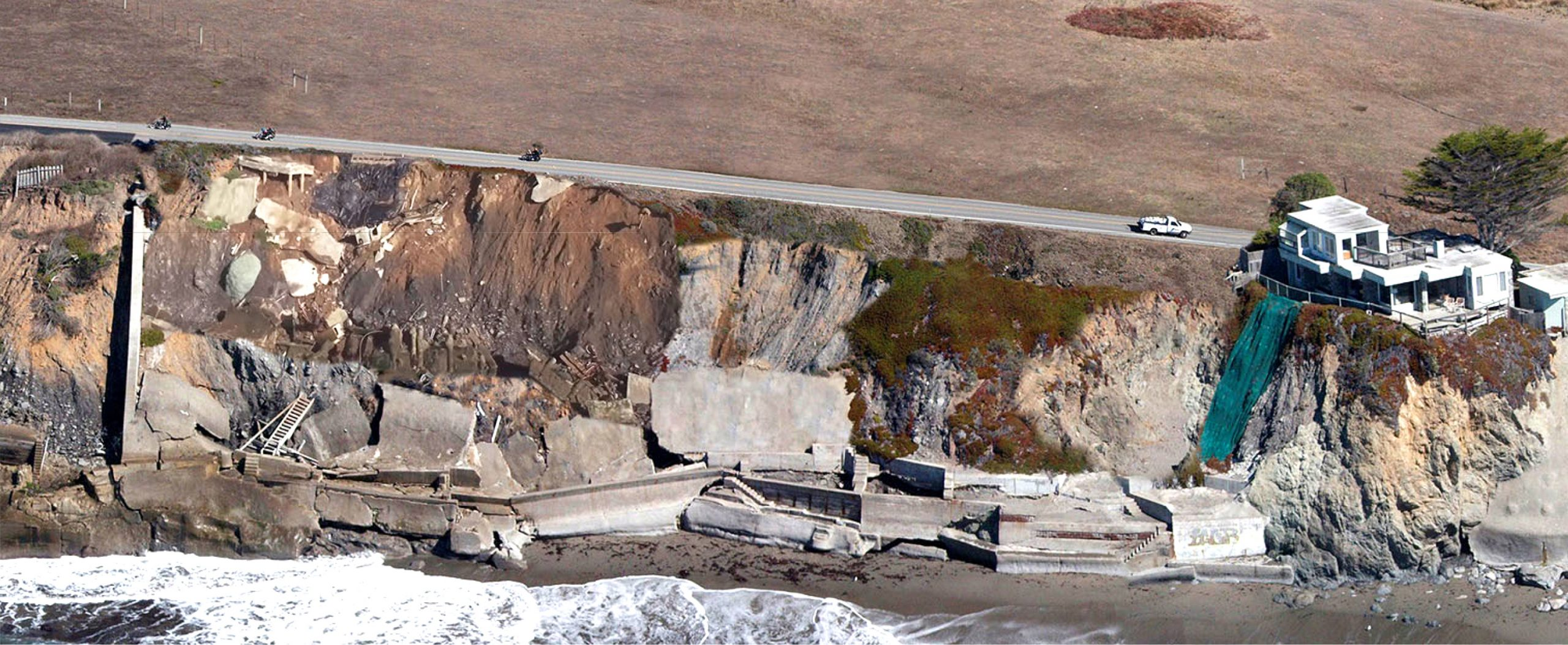 Photo of coastal erosion having destroyed several houses and encroaching on SR1.
